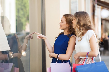 woman shop: sale, consumerism and people concept - happy young women with shopping bags pointing finger to shop window in city Stock Photo