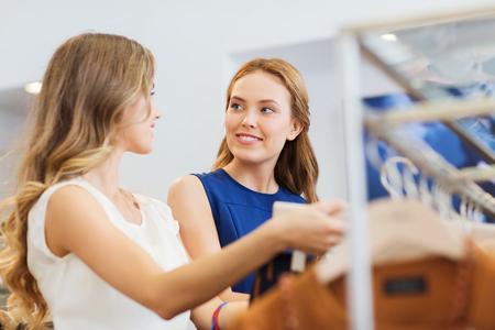 sprzedaż, konsumpcjonizm i koncepcja ludzi - szczęśliwe młode kobiety z torby na zakupy wybierając ubrania w sklepie odzieżowym