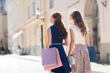 view girl: sale, consumerism and people concept - happy young women with shopping bags walking along city street