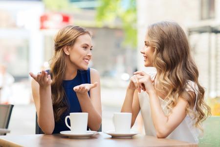 사람들, 통신 및 우정 개념 - 커피 또는 차를 마시는 야외 카페에서 얘기하는 젊은 여성의 미소 스톡 콘텐츠