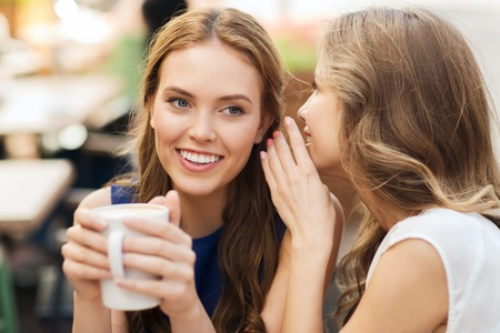 Menschen, Kommunikation und Freundschaft Konzept - lächelnde junge Frauen trinken Kaffee oder Tee und Tratsch am Café im Freien
