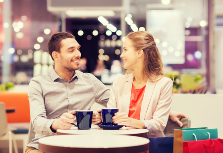 centro comercial: venta, compras, consumismo, el ocio y el concepto de la gente - pareja feliz con bolsas de la compra que beben el café en el centro comercial Foto de archivo