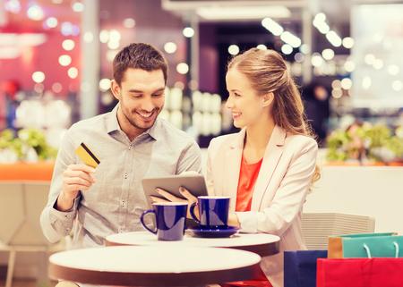 tarjeta de credito: venta, compras, consumismo, el ocio y el concepto de la gente - la feliz pareja con Tablet PC y la tarjeta de crédito el consumo de café en el centro comercial