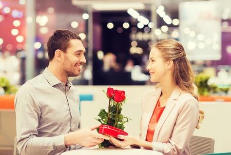romantik: kärlek, romantik, Alla hjärtans dag, par och människor begrepp - lycklig ung man med röda blommor som ger present till leende kvinna på cafe i köpcentret Stockfoto