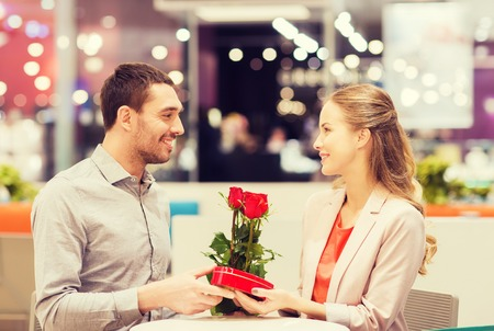 romance: love, romance, valentines day, couple and people concept - happy young man with red flowers giving present to smiling woman at cafe in mall