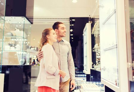 consumerism: sale, consumerism and people concept - happy couple looking to shopping window at jewelry store in mall