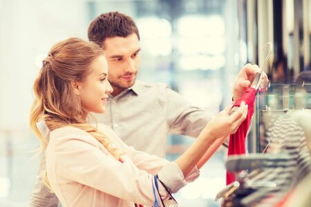plaza comercial: venta, el consumismo y el concepto de la gente - joven pareja feliz con bolsas de la compra que eligen la alineada en el centro comercial Foto de archivo