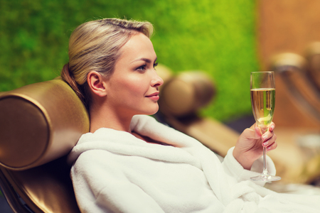 bath robe: people, beauty, lifestyle, holidays and relaxation concept - beautiful young woman in white bath robe lying on chaise-longue and drinking champagne at spa