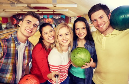 la gente, el ocio, el deporte, la amistad y el concepto de entretenimiento - amigos felices que toman Autofoto con smartphone en monopod en club del bowling