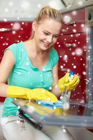 cleanser: people, housework and housekeeping concept - happy woman with bottle of spray cleanser cleaning oven at home kitchen over snow effect Stock Photo