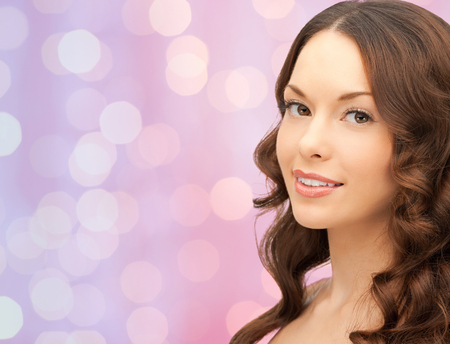 young woman face: beauty, people and health concept - beautiful young woman face over pink lights background