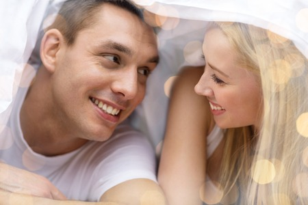 day bed: people, love, relations and bedtime concept - happy couple under blanket in bed over lights background