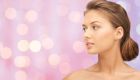 human nose: beauty, people and health concept - beautiful young woman face over pink background