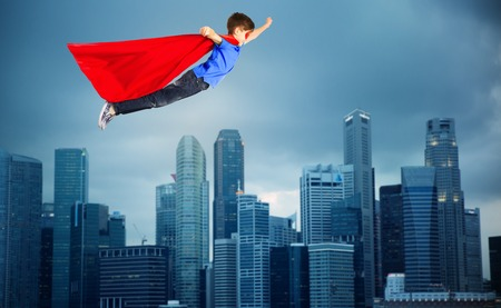 air movement: happiness, freedom, childhood, movement and people concept - boy in red superhero cape and mask flying in air over city background