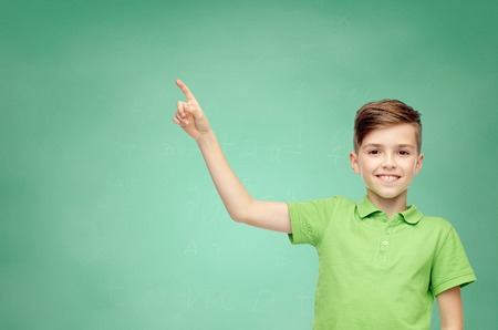 childhood, education and people concept - happy smiling boy in green polo t-shirt pointing finger up over green school chalk board background Banco de Imagens