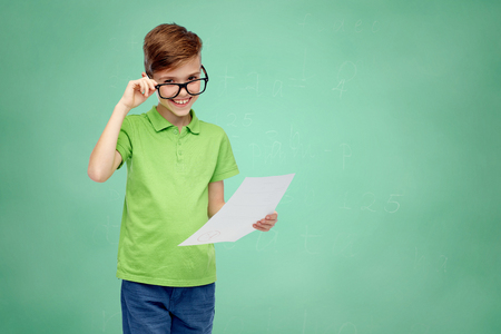 pre teen boy: childhood, school, education and people concept - happy smiling boy in eyeglasses holding paper with test result over green school chalk board background