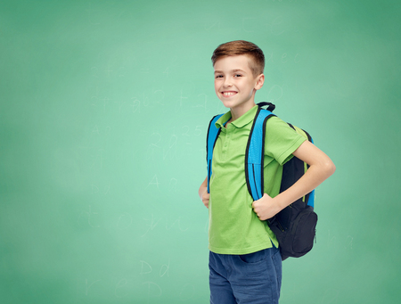 school board: childhood, school, education and people concept - happy smiling student boy with school bag over green school chalk board background