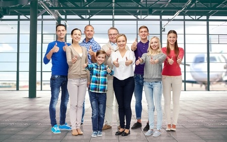 a big family: gesture, travel, tourism and people concept -  big happy family showing thumbs up over airport terminal background Stock Photo