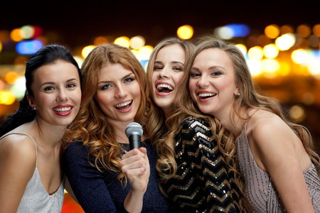 karaoke singer: holidays, friends, bachelorette party, nightlife and people concept - three women in evening dresses with microphone singing karaoke over lights background