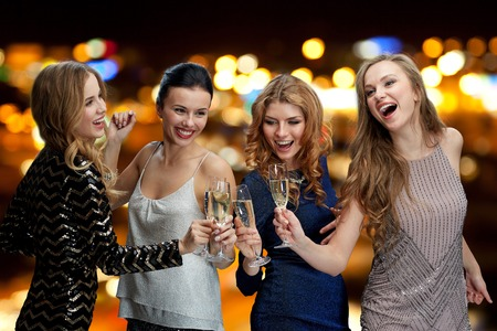 sparkling wine: celebration, friends, bachelorette party, nightlife and holidays concept - happy women clinking champagne glasses and dancing over night lights background