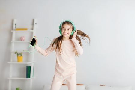 personas saltando: gente, niños, fiesta de pijamas y concepto de la tecnología - niña sonriente feliz en los auriculares que saltan en cama con el teléfono inteligente y escuchar música en casa Foto de archivo