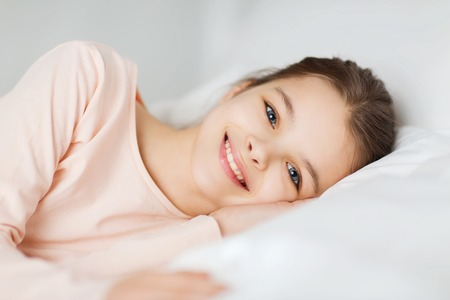 wellness sleepy: people, children, rest and comfort concept - happy smiling girl lying awake in bed at home