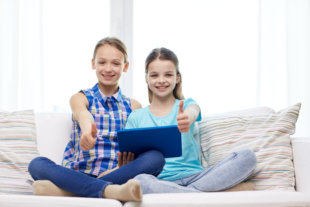 pre approval: people, children, gesture, friends and friendship concept - happy little girls with tablet pc computer sitting on sofa and showing thumbs up at home