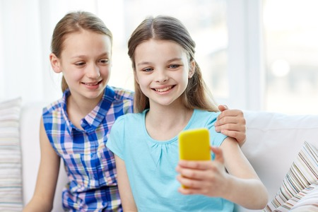 child portrait: people, children, technology, friends and friendship concept - happy little girls sitting on sofa and taking selfie with smartphone and hugging at home