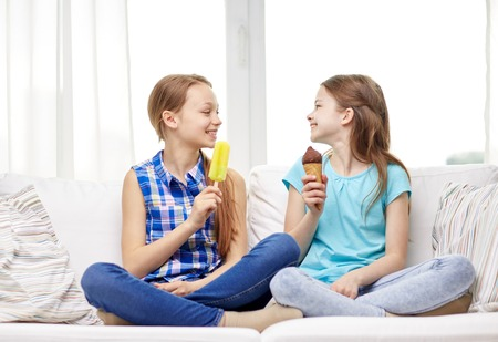 people, children, friends and friendship concept - happy little girls eating ice-cream at home