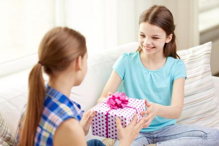 niños sentados: gente, niños, días de fiesta, amigos y el concepto de la amistad - niñas felices con regalo de cumpleaños sentado en el sofá en casa