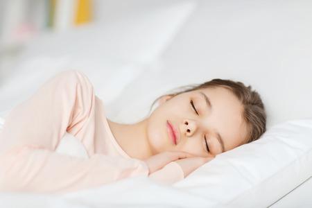 ni�as peque�as: la gente, los ni�os, el descanso y la comodidad concepto - ni�a durmiendo en la cama en su casa