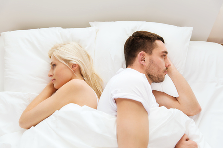conflict: people, relationship difficulties, conflict and family concept - unhappy couple lying back to back in bed at home