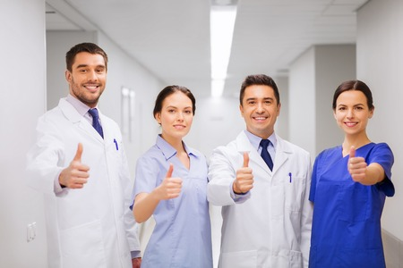 thumbs up group: profession, people, health care, gesture and medicine concept - group of happy medics or doctors at hospital corridor showing thumbs up
