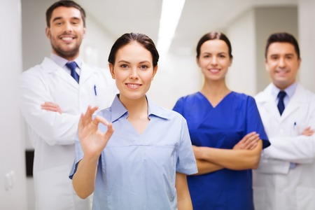 ok hand: clinic, profession, people, health care and medicine concept - group of happy medics or doctors at hospital corridor showing ok hand sign Stock Photo