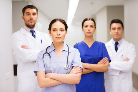 serious doctor: clinic, profession, people, health care and medicine concept - group of medics or doctors at hospital corridor Stock Photo