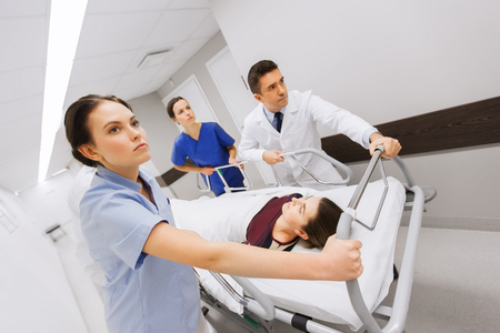 profesión, la gente, la atención sanitaria, la reanimación y el concepto de la medicina - grupo de médicos o médicos que llevan la mujer paciente en la camilla del hospital de emergencia