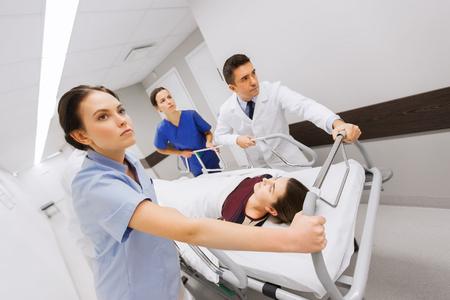 lesionado: profesión, la gente, la atención sanitaria, la reanimación y el concepto de la medicina - grupo de médicos o médicos que llevan la mujer paciente en la camilla del hospital de emergencia