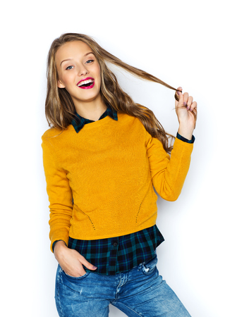 cute teen: people, style, hairstyle and fashion concept - happy young woman or teen girl in casual clothes holding her hair strand
