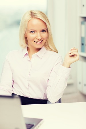 computer office: education, business and technology concept - smiling businesswoman or student with laptop computer in office