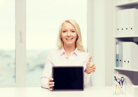 education, business, gesture and technology concept - smiling businesswoman or student showing thumbs up and tablet pc computer blank screen in office