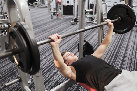 benches: sport, bodybuilding, lifestyle and people concept - young man with barbell flexing muscles and making bench press in gym