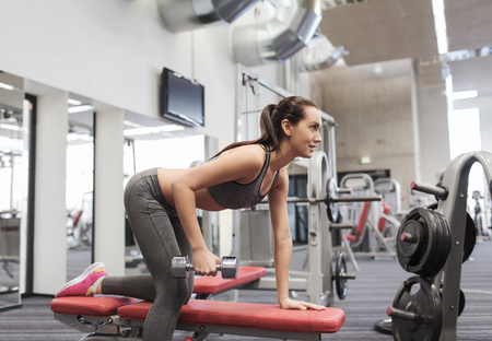 Weights: fitness, sport, training and people concept - smiling woman with dumbbell flexing muscles on bench in gym