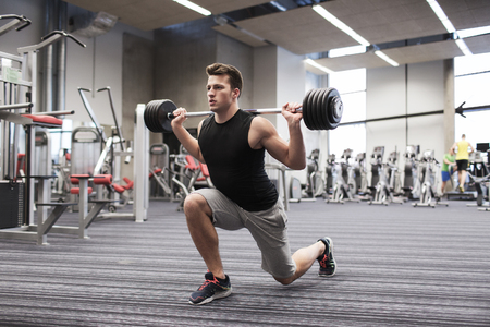 lunge: sport, bodybuilding, lifestyle and people concept - young man with barbell flexing muscles and making shoulder press lunge in gym Stock Photo