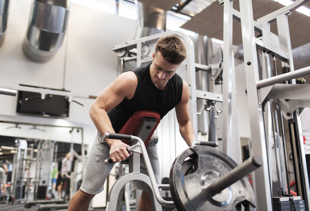 t bar: sport, bodybuilding, equipment and people concept - young man with barbell flexing muscles on t-bar row machine in gym Stock Photo