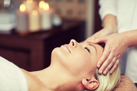 head massage: people, beauty, spa, healthy lifestyle and relaxation concept - close up of beautiful young woman lying with closed eyes and having face or head massage in spa Stock Photo