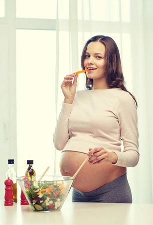woman pregnant: pregnancy, cooking food, healthy lifestyle, people and expectation concept - happy pregnant woman mixing vegetable salad in bowl at home