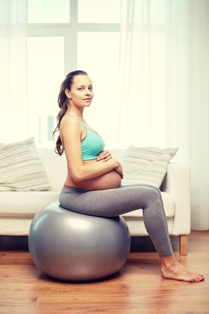 gymnastics: pregnancy, sport, fitness, people and healthy lifestyle concept - happy pregnant woman exercising on fitball at home