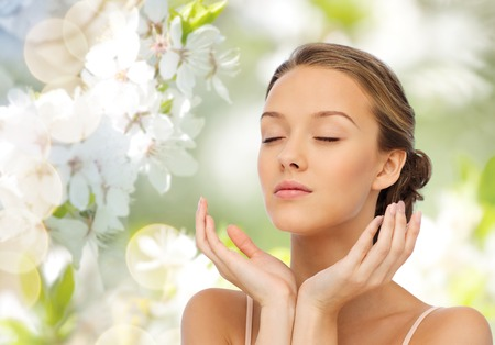 beauty, people, skincare, summer and health concept - young woman face and hands over green natural background with cherry blossom Stock Photo