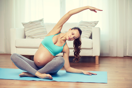 big belly: pregnancy, sport, yoga, people and healthy lifestyle concept - happy pregnant woman exercising and stretching on mat at home