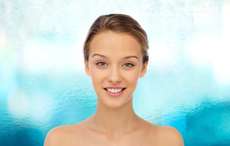 la belleza, la gente y el concepto de salud - joven cara y los hombros sobre el fondo del agua azul sonriente